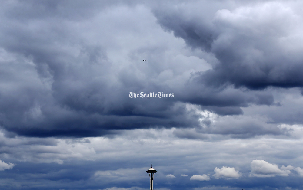 The Space Needle looks tiny under these massive cloud formations seen from West Seattle. (Ken Lambert/The Seattle Times)