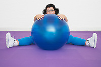 Uninspired overweight Woman sitting Behind Exercise Ball