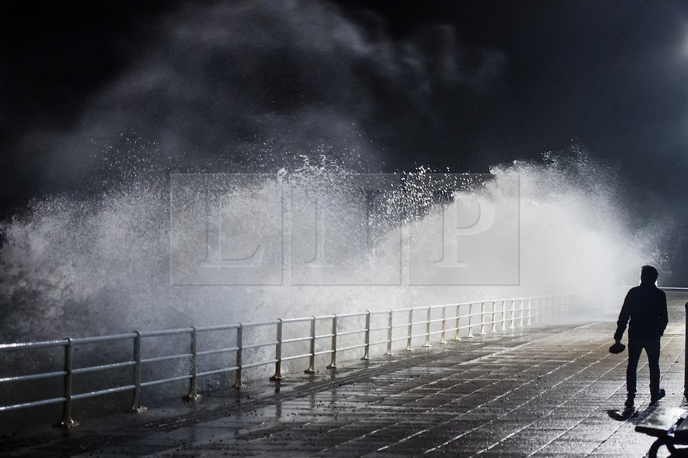 © London News Pictures. 12/11/2015/ Aberystwyth, Wales, UK. As Storm Abigail picks up strength and heads towards the west and north of the UK, people watch as huge waves batter the seafront in Aberystwyth Wales. Photo credit: Keith Morris/LNP