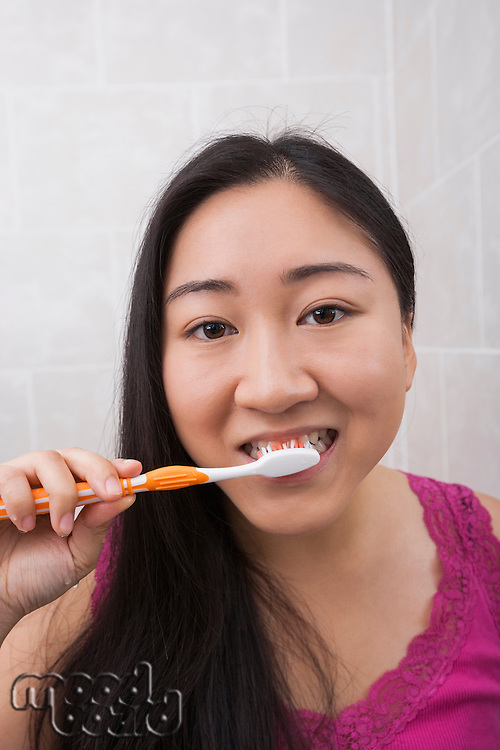 Close-up view of young Asian woman brushing her teeth in bathroom