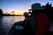 Tourist on a boat trip in the Pantanal before sunrise, Mato Grosso, Brazil