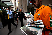 """Trouble on Wall Street. A man hands out the Metro newspaper which has the headline """"Wall Street Massacre"""" on the front. The newspaper headline came after the start of the 2008 recession caused by failing housing market and subprime bundling scandal."""