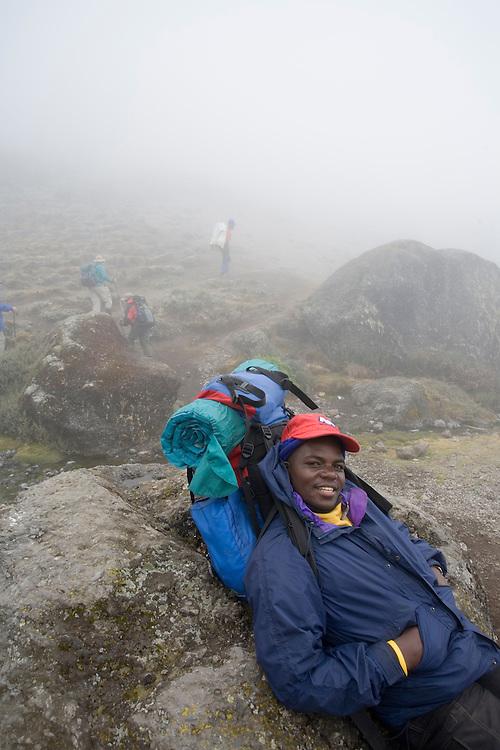 Africa, Tanzania, Kilimanjaro National Park, (MR) Climbing resting in fog along trail near Karanga Camp (13000')  on climbing expedition