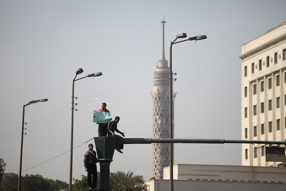 Protesters stand atop a light post, the Cairo Tower is seen in the background.