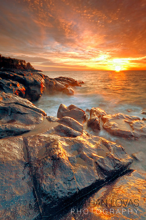 Sunset with orange sky and wet rocks along North Shore of Lake Superior;  Temperance River State Park, MInnesota.