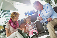 Portrait of mature man playing airplane with his cute daughter in airport while waiting for boarding