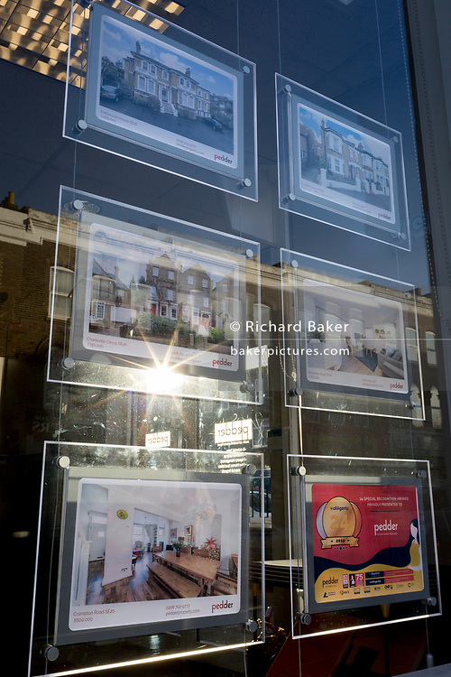 Sunlight bursts through the images of properties and their details being represented by south London estate agent Pedder in Sydenham, on 5th February 2020, in London, England.