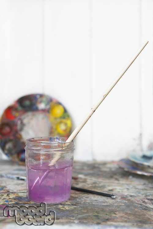 Still life of paintbrush resting in jar of purple water