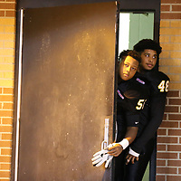 Pontotoc players Myles Chewe and Jay Whitefiled peak out of their lockeroom before Thursday's game with Shannon. The game was moved up from Friday to avoid rainy weather.