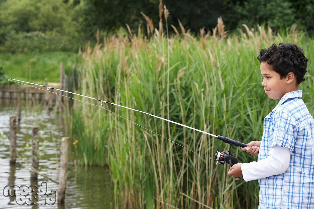 Boy (7-9) fishing in river