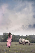 a woman in a pink dress is walking towards some wild ponies