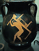 Athenian red-figure pottery pelike, found in Gela, Sicily, fifth century BC.  A slave-boy carrying furniture (a couch and a table) for a symposium.