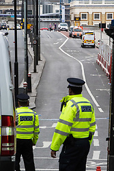 London, June 4th 2017. Police officers look along London Bridge towards Borough High Street during a massive policing operation in the aftermath of the terror attack on London Bridge and Borough Market on the night of June 3rd which left seven people dead and dozens injured