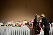 """Samantha Tischler (right) and Brittany Mclintire (left) talk about the selection of purses availible at the """"Power of the Purse"""" silent  auction during the Women in Philanthropy conference on Thursday, March 14th in Baker Ballroom. Photo by: Ross Brinkerhoff."""