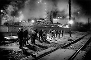 A cluster of migrants from Central America mill around in the pre-dawn chill of 2,200m (6,000 ft) high Valley of Mexico waiting for the freight train north to depart, Lecheria, Mexico City, Mexico.