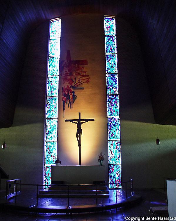Steinkjer kirke fra 1965. Glassvinduene i kirka er et av kunstneren Jakob Weidemanns hovedverk. Weidemann har også laget det nonfigurative maleriet på veggen bak alteret.