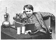 Thomas Alva Edison (1847-1931) American inventor, listening to a recording on his phonograph. This is an electric model powered by a bichromate cell (left), a form of wet battery. Engraving c1895.