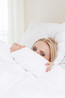 Portrait of shy young woman hiding under bedsheet