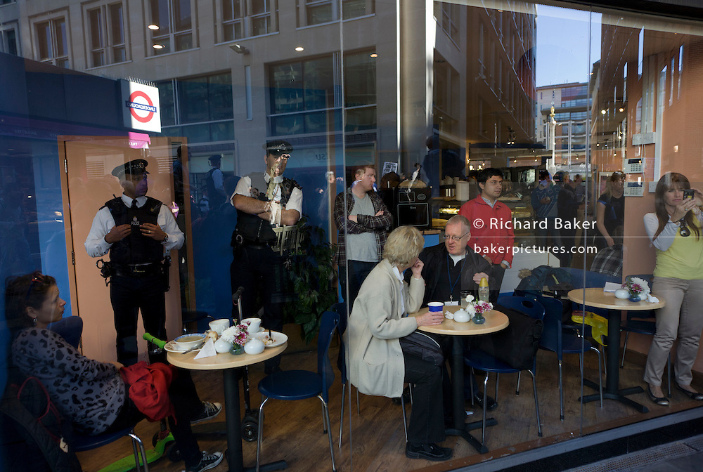 Accompanied by Metropolitan police officers, cafe diners remain inside during world corporate greed and government austerity measures protests.
