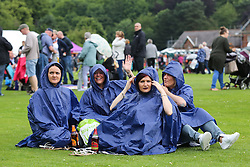 © Licensed to London News Pictures. 09/07/2016. Durham, UK. Day-trippers shelter from the rain under their ponchos at the Durham Miners' Gala in County Durham, UK. The gala is a large gathering held annually associated with the coal mining heritage and trade unionism. Photo credit : Ian Hinchliffe/LNP