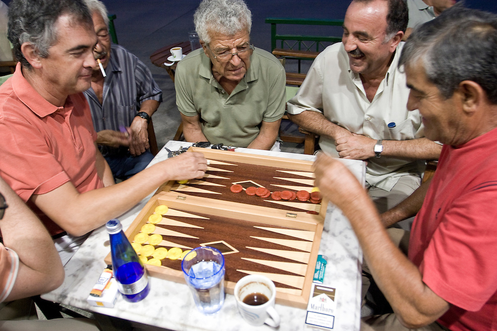 PRIGI, GREECE: A group of men play backgammon on the streets of Prigi in Chios island, Greece.