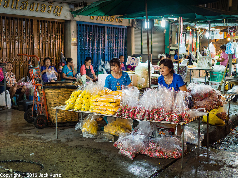 24 FEBRUARY 2016 - BANGKOK, THAILAND:  Women sell flower garlands on the sidewalk before sunrise in front of Pak Khlong Talat in Bangkok. Bangkok government officials announced this week that vendors in Pak Khlong Talat, Bangkok's well known flower market, don't have to move out on February 28. City officials are trying to clear Bangkok's congested sidewalks and they've cracked down on sidewalk vendors. Several popular sidewalk markets have been closed in recent months and the sidewalk vendors at the flower market had been told they would be evicted at the end of the month but after meeting with vendors and other stake holders city officials relented and said vendors could remain but under stricter guidelines regarding sales hours. The flower market is one of the best known markets in Bangkok and has become a popular tourist destination.       PHOTO BY JACK KURTZ