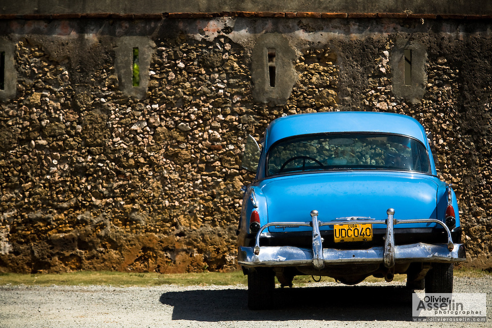A 1950s-era vintage automobile is parked outside a colonial fort in Baracoa, Cuba on Monday July 14, 2008.