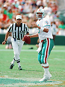 An NFL referee looks on as Miami Dolphins quarterback Dan Marino (13) throws a pass from his tip toes during the 1992 NFL regular season football game against the Atlanta Falcons on Oct. 11, 1992 in Miami. The Dolphins won the game 21-17. (©Paul Anthony Spinelli)