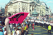 Ravers marching with the Liberty flag through Piccadilly Circus,protesting against the first Criminal Justice Act. London, UK, 1st of May 1994.