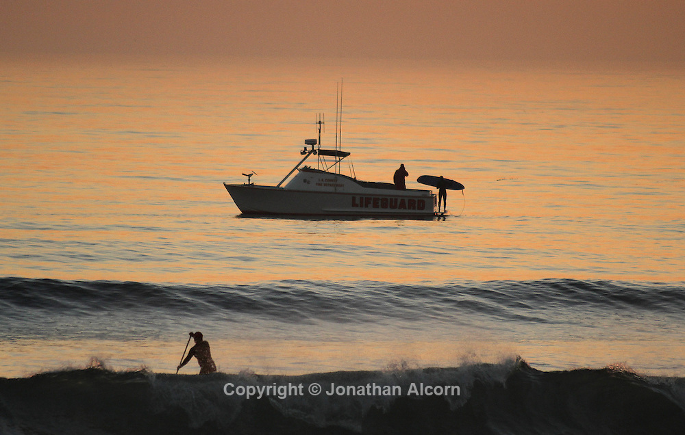 A paddle boarder paddles through the surf zone while a surfer boards a Los Angeles County Lifeguard boat at the beach where Sunset Blvd ends at Pacific Coast Highway on a warm January winter day.