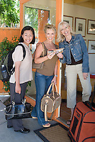 Three women with luggage on vacation, portrait