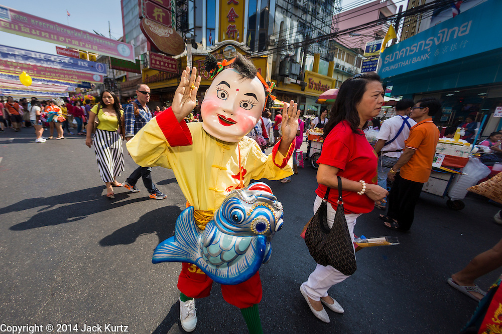 31 JANUARY 2014 - BANGKOK, THAILAND:   A member of a Lion dance troupe walks down a street during Lunar New Year festivities, also know as Tet and Chinese New Year, in Bangkok. This year is the Year of the Horse. The Lion Dance scares away evil spirits and brings prosperity and luck. Ethnic Chinese make up about 14% of Thailand and Chinese holidays are widely celebrated in Thailand.     PHOTO BY JACK KURTZ