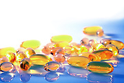 Various yellow and orange pills and capsules on a blue and white background with saturated colors and copy space