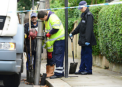 © Licensed to London News Pictures. 30/08/2012. London, UK Police search the drains in the street. A street cleaner has suffered potentially life threatening after being stabbed when disturbing a burglary in Shepherds Bush in West London today 30 August 2012. Photo credit : Stephen Simpson/LNP