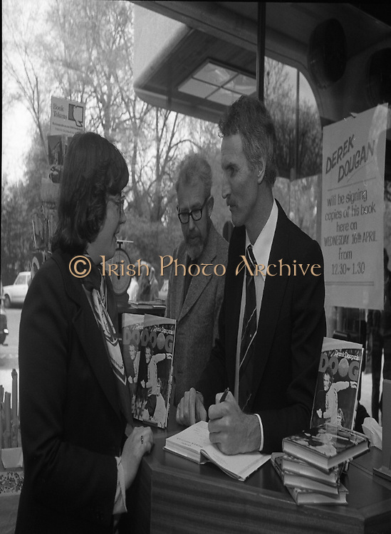 Derek Dougan's name goes in the book...1980-04-16.16th April 1980.16-04-1980.04-16-80..Photographed at Hodges Figgis, Stephen's Court, St Stephen's Green, Dublin:..Fromer Northern Irish soccer international and English League player Derek Dougan signing a copy of his book 'Doog' for customer Anne Carey, Templeogue. ..Also in picture..Robert Twigg, manager of Hodges Figgis .