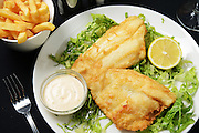 A plate of fried Fish and Chips served on lettuce