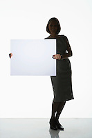 Silhouetted woman standing holding large blank card to side