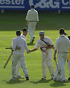 Photo Peter Spurrier.01/09/2002.Village Cricket Final - Lords.Elvaston C.C. vs Shipton-Under-Wychwood C.C..Shipton's batsman Shane Duff (left) and Chris Panter skake hands after scoring the winning run (Duff) as a dejected Elvaston leave the field.