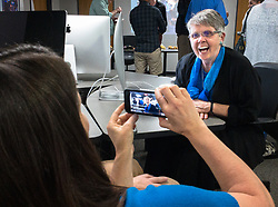A reception was held for Rita Reed, photojournalism professor at the Missouri School of Journalism, to celebrate her retirement after 16 years of being on the faculty. <br /> <br /> In this photo, Reed (right) speaks with former students, colleagues and friends via a live chat session. Holding the cellphone camera for the session is Jackie Bell, associate professor of photojournalism. Reed and Bell are co-directors of the College Photographer of the Year Competition.<br /> <br /> The event was held on May 10, 2017 in the Cliff and Vi Edom Photojournalism Lab in Lee Hills Hall on the University of Missouri campus in Columbia, Mo.<br /> <br /> The following is from Reed&rsquo;s bio posted on the Missouri School of Journalism website: &quot;Rita Reed joined the photojournalism faculty in 2001 after 20 years as a working photojournalist with Star Tribune in Minneapolis and The Gazette in Cedar Rapids, Iowa. She has worked not only on local, regional and national stories, but also internationally in Haiti, Bolivia, Colombia, Taiwan, China and the countries of the former Eastern Block.<br /> <br /> Reed holds a master&rsquo;s degree in journalism from the University of Missouri and an undergraduate degree from Southwest Missouri State University. She was the 1993 recipient of the Nikon Sabbatical Grant for Documentary Photography for the completion of work on a photographic book about gay and lesbian teenagers. Reed maintains an interest in and concern for adolescents and the issues they face. She is the director of the College Photographer of the Year competition.&rdquo;