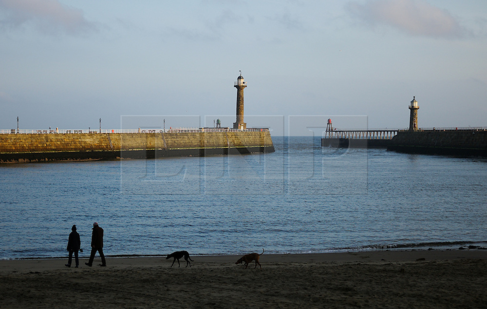 &copy; Licensed to London News Pictures. <br /> 15/03/2015. <br /> <br /> Whitby, United Kingdom<br /> <br /> A couple walk their dogs on the beach at first light in Whitby in North Yorkshire.<br /> <br /> Photo credit : Ian Forsyth/LNP