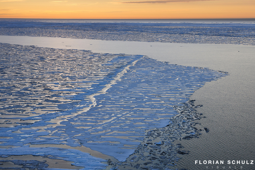 By the end of June large leads are created by currents and wind in the sea ice of the Beaufort Sea. The arctic sun never sets during the summer months. It rather skimms the ocean`s horizon to the north. Beaufort Sea, Alaska