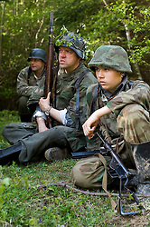 Reenactors from Northern World War Two Association, dressed as Panzer Grenadiers from the Elite Grossdeutschland Division, waiting for the return of reconnaissance party during a private 24hr excerise, held at Sutton Grange, near Ripon in Yorkshire. All are wearing the iconic coal scuttle helmets (stahlhelme) splinter pattern camouflage and Jackboots One reenactor is holding the K98 Rifle and in the foreground is a German MP3008 sub machine gun which was based on the British Sten gun.<br />