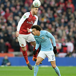 Calum Chambers of Arsenal challenges for the ariel ball with Leroy Sane of Manchester City