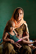 """Shashi Devi (aged 28) sits for a portrait in her house in the village of Shahpurjat, Ghaziabad, Uttar Pradesh, India. While Shashi had a tubectomy done after having 2 sons, Monika, her brother-in-law's wife, is still trying for a son after having 2 daughters. Shashi did the operation because she wanted to """"give her 2 children the best and inflation will make things difficult"""", and she believes that a """"small family = happy family"""". She has been pushing Monika to get her husband to do an NSV so that Monika's life is not endangered since her previous pregnancies have been complicated. Photo by Suzanne Lee / Panos London"""