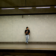 A young man waits for the train at Sao Bento metro station in Porto.