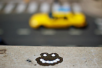 A happy face made of milkshake drops melts under the afternoon sun Friday, Sept. 16 2011 as a yellow cab along a downtown Denver street.