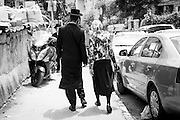 A young married couple of religious Jews walks on a little traverse from Me'A  She'arim Street in Jerusalem on a Tuesday afternoon. The short hat worned by the man and the hancarchif worned by the woman identify them, most likely, as decendent from one of the largest orthodox dynasty existing, the Satmar, from Hungary.