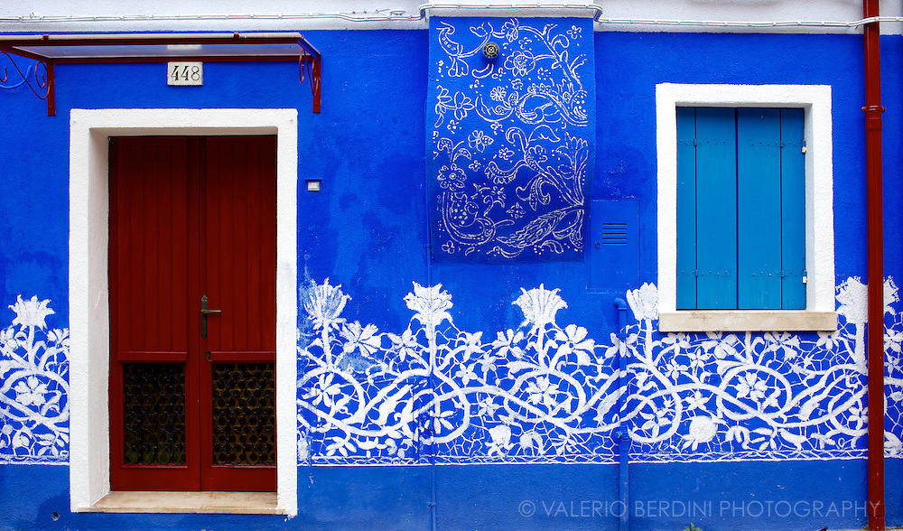 The facade of one of the houses in Burano which recall at the same time both the traditions of the island: the bright coloured walls and the needle lace.