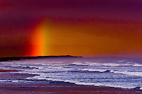 Rainbow behind crashing waves at Strandfontein (near Cape Town), South Africa