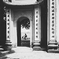 A girl rides her bicycle past a temple gate in Hanoi, Vietnam.